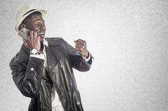 Νέος αφρικανικός τύπος που εξετάζει το τηλέφωνο κυττάρων Στοκ Φωτογραφίες