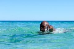 Νέος αφρικανικός τύπος που κολυμπά στο ωκεάνιο νερό Στοκ Φωτογραφία