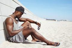 Νέος αφρικανικός τύπος που στέλνει ένα μήνυμα κειμένου στην παραλία Στοκ φωτογραφία με δικαίωμα ελεύθερης χρήσης