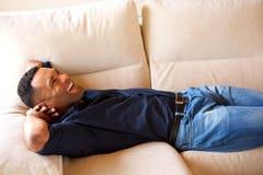 Νέος αφρικανικός τύπος που στηρίζεται στον καναπέ και που χαμογελά στο σπίτι Στοκ φωτογραφία με δικαίωμα ελεύθερης χρήσης
