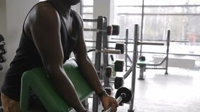 Νέος αφροαμερικανός αθλητής που κάνει την μπούκλα δικέφαλων μυών barbell στη γυμναστική φιλμ μικρού μήκους