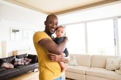Νέος αφροαμερικανός πατέρας που κρατά το γιο μωρών του στα όπλα στοκ φωτογραφία