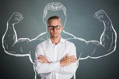 Νέος βέβαιος επιχειρηματίας με το σχεδιασμό μυών βραχιόνων Στοκ Φωτογραφίες
