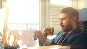 Νέος βέβαιος επιχειρηματίας που εργάζεται στον υπολογιστή και το τσάι κατανάλωσής του Στοκ εικόνα με δικαίωμα ελεύθερης χρήσης