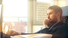 Νέος βέβαιος επιχειρηματίας που εργάζεται στον υπολογιστή του στο ηλιοφώτιστο γραφείο Στοκ εικόνα με δικαίωμα ελεύθερης χρήσης
