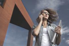 Νέος, βέβαιος, επιχειρησιακή γυναίκα στη βιασύνη Ομιλία στο smartphone περπατώντας κάτω από την οδό στοκ εικόνες
