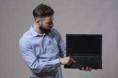 Νέος βέβαιος επιχειρησιακός άτομο ή προγραμματιστής χρησιμοποιώντας τον υπολογιστή και προσέχοντας το όργανο ελέγχου lap-top Στοκ Εικόνες