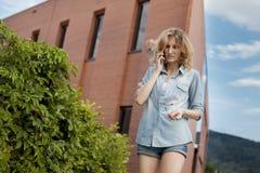 Νέος βέβαιος σπουδαστής που περπατά στη βιασύνη, που μιλά στο κινητό τηλέφωνο στην οδό πόλεων Στοκ Φωτογραφίες