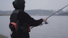 Νέος βέβαιος ψαράς πορτρέτου στην περιστροφή ξημερωμάτων που αλιεύει στον ποταμό κοντά στην πόλη Αλιεύοντας ράβδος και ένα εξέλικ φιλμ μικρού μήκους