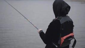 Νέος βέβαιος ψαράς πορτρέτου στην περιστροφή ξημερωμάτων που αλιεύει στον ποταμό κοντά στην πόλη Αλιεύοντας ράβδος και ένα εξέλικ απόθεμα βίντεο