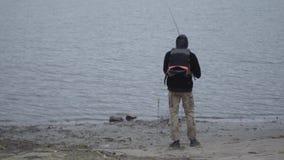 Νέος βέβαιος ψαράς στα χακί εσώρουχα στα ξημερώματα που πιάνουν τα ψάρια στην περιστροφή στον ποταμό κοντά στην πόλη απόθεμα βίντεο