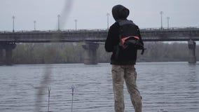 Νέος βέβαιος ψαράς στα χακί εσώρουχα στην περιστροφή ξημερωμάτων που αλιεύει στον ποταμό κοντά στην πόλη Αλιεύοντας ράβδος και α απόθεμα βίντεο
