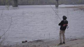 Νέος βέβαιος ψαράς στην περιστροφή ξημερωμάτων που αλιεύει στον ποταμό κοντά στην πόλη Αλιεύοντας ράβδος και ένα εξέλικτρο Μύγα απόθεμα βίντεο