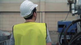 Νέος βιομηχανικός μηχανικός που περπατά μέσα στις εγκαταστάσεις εργοστασίων και που ελέγχει στην κατασκευή των μηχανών απόθεμα βίντεο