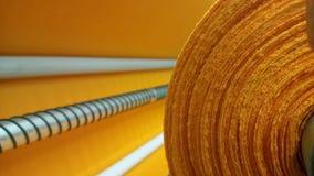 Νέος βιομηχανικός πορτοκαλής ρόλος, πορτοκαλί υπόβαθρο Έννοια: υλικό, ύφασμα, κατασκευή, εργοστάσιο ενδυμάτων, νέα δείγματα των υ στοκ εικόνα