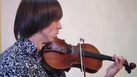 Νέος βιολιστής στο μπλε παιχνίδι πουκάμισων σχεδίων στον εορτασμό μουσικός Απόδοση φιλμ μικρού μήκους