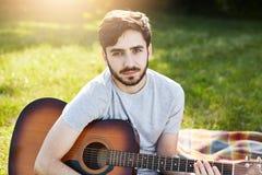Νέος γενειοφόρος αρσενικός κιθαρίστας στην περιστασιακή συνεδρίαση μπλουζών με το μουσικό όργανο στην πράσινη χλόη, παίζοντας δια στοκ εικόνα με δικαίωμα ελεύθερης χρήσης