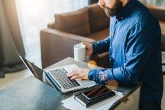 Νέος γενειοφόρος επιχειρηματίας που εργάζεται στον υπολογιστή στον πίνακα, καφές κατανάλωσης Το άτομο αναλύει τις πληροφορίες, στ Στοκ Φωτογραφία