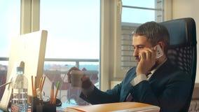 Νέος γενειοφόρος επιχειρηματίας που εργάζεται στον υπολογιστή του, talkink στο τηλέφωνο κυττάρων και κατοχή του καφέ στο γραφείο Στοκ Εικόνες