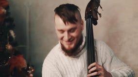 Νέος γενειοφόρος μουσικός με τις slapping σειρές παιχνιδιού mohawk contrabass απόθεμα βίντεο
