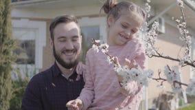 Νέος γενειοφόρος πατέρας πορτρέτου που ανυψώνει τη μικρή χαμογελώντας κόρη του έτσι θα μπορούσε να μυρίσει το άνθος δέντρων κοντά απόθεμα βίντεο