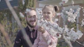 Νέος γενειοφόρος πατέρας πορτρέτου που κρατά τη μικρή χαμογελώντας κόρη του στα όπλα του έτσι θα μπορούσε να μυρίσει το άνθος δέν απόθεμα βίντεο