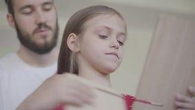 Νέος γενειοφόρος πατέρας που βάζει την κορώνα στο κεφάλι του μικρού κοριτσιού του, που κάνει την πριγκήπισσά της ενώ το παιδί που απόθεμα βίντεο