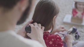 Νέος γενειοφόρος πατέρας που βουρτσίζει την τρίχα του μικρού κοριτσιού του ενώ το παιδί που κτενίζει τη συνεδρίαση παιχνιδιών της φιλμ μικρού μήκους