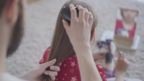 Νέος γενειοφόρος πατέρας που βουρτσίζει την τρίχα του μικρού κοριτσιού του ενώ το παιδί που κτενίζει τη συνεδρίαση παιχνιδιών της απόθεμα βίντεο