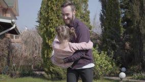 Νέος γενειοφόρος πατέρας που κρατά τη μικρή χαμογελώντας κόρη του στα όπλα του που περιστρέφουν γύρω, και το δύο γέλιο : απόθεμα βίντεο