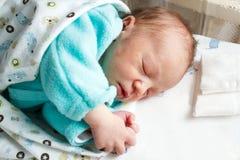Νέος - γεννημένος ύπνος μωρών με τα χέρια που διπλώνονται Στοκ φωτογραφία με δικαίωμα ελεύθερης χρήσης