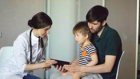Νέος γιατρός γυναικών που μιλά με τον πατέρα του μικρού παιδιού που χρησιμοποιεί τον υπολογιστή ταμπλετών στο ιατρικό γραφείο Στοκ φωτογραφία με δικαίωμα ελεύθερης χρήσης