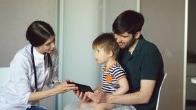 Νέος γιατρός γυναικών που μιλά με τον πατέρα του μικρού παιδιού που χρησιμοποιεί τον υπολογιστή ταμπλετών στο ιατρικό γραφείο Στοκ φωτογραφίες με δικαίωμα ελεύθερης χρήσης