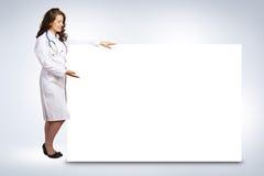 Νέος γιατρός γυναικών που στέκεται κοντά σε ένα κενό έμβλημα Στοκ εικόνα με δικαίωμα ελεύθερης χρήσης
