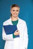 Νέος γιατρός γυναικών σπουδαστών με μια ταμπλέτα σε ένα μπλε υπόβαθρο που παρουσιάζει σημάδια Στοκ Εικόνα