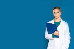 Νέος γιατρός γυναικών σπουδαστών με μια ταμπλέτα σε ένα μπλε υπόβαθρο που παρουσιάζει σημάδια Στοκ Εικόνες