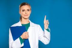 Νέος γιατρός γυναικών σπουδαστών με μια ταμπλέτα σε ένα μπλε υπόβαθρο που παρουσιάζει σημάδια Στοκ Φωτογραφία