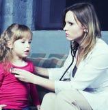 Νέος γιατρός με τον ασθενή μικρών κοριτσιών που αισθάνεται την κακή ιατρική επιθεώρηση Στοκ Φωτογραφίες