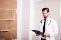 Νέος γιατρός με το στηθοσκόπιο arround ο λαιμός του στο νοσοκομείο recov Στοκ Εικόνες