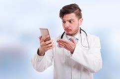 Νέος γιατρός που εξετάζει μπερδεμένος το τηλέφωνό του Στοκ φωτογραφία με δικαίωμα ελεύθερης χρήσης