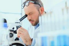 Νέος γιατρός στην ομοιόμορφη εργασία στη δοκιμή του εργαστηρίου στην κλινική Στοκ Φωτογραφίες