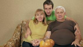 Νέος γιος ενός ηλικιωμένου ζεύγους που αγκαλιάζει στο σπίτι στον καναπέ Ο καθένας εξετάζει τη κάμερα και το χαμόγελο Επικοινωνούν φιλμ μικρού μήκους