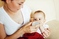 Νέος γιος μωρών μικρών παιδιών εκμετάλλευσης μητέρων brunette ευτυχής, στήθος-αμοιβή στοκ φωτογραφία