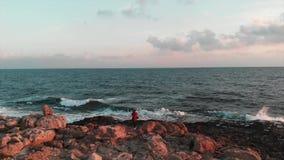 Νέος γοητευτικός θηλυκός τουρίστας που παίρνει τις εικόνες του όμορφου ωκεανού με τα μεγάλα κύματα στο ρόδινο ηλιοβασίλεμα στην ε απόθεμα βίντεο