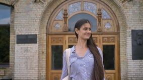 Νέος γοητευτικός σπουδαστής brunette με τη μακρυμάλλη μετάβαση μακρυά από το κολλέγιο και το χαιρετισμό κάποιου έξω, εύθυμος και  απόθεμα βίντεο