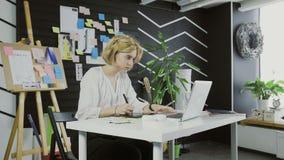 Νέος γραφικός σχεδιαστής γυναικών που χρησιμοποιεί την ταμπλέτα γραφικής παράστασης απόθεμα βίντεο