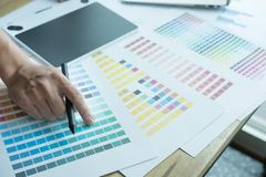 Νέος γραφικός σχεδιαστής που εργάζεται με τον υπολογιστή και swatch χρώματος Γ Στοκ Φωτογραφία