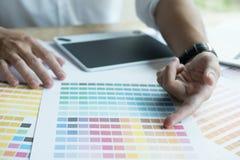 Νέος γραφικός σχεδιαστής που εργάζεται με τον υπολογιστή, swatch χρώματος Crea Στοκ Εικόνες