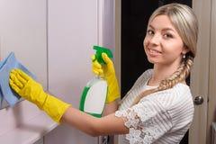 Νέος γυναικείος σκουπίζοντας καθρέφτης με το μπλε ύφασμα και τον ειδικό καθαρισμό Στοκ Εικόνα