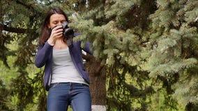 Νέος γυναικών πυροβολισμός διαδικασίας φωτογράφων λειτουργώντας υπαίθρια στη φύση πάρκων φιλμ μικρού μήκους